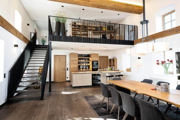ein Raum mit Stiege und Geschoß; Tisch, Küche.