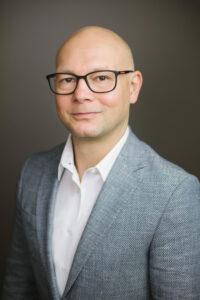 Mann mit Brille und Anzug vor grauem Hintergrund