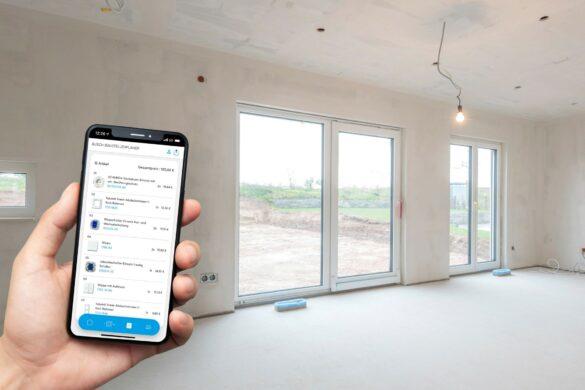 Hand mit Smartphone in einem leeren Raum mit Fenstern