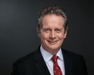 Mann in Anzug und roter Krawatte vor schwarzem Hintergrund