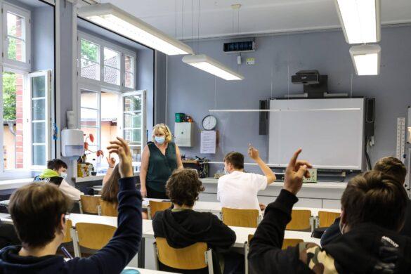 Kinder heben in der Klasse ihre Hände